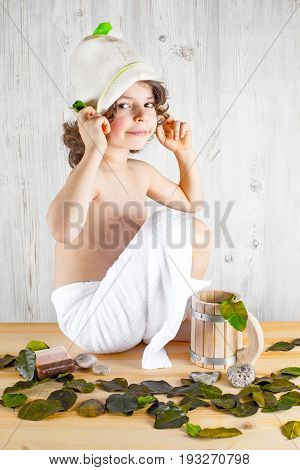 Cute Curly-haired Boy Shirtless In A Towel Sitting Clothes Felt Hat, Smiling, Looking Into The Camer