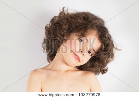Young Curly-haired Boy Tilted His Head Looking At The Camera. Close-up. Gray Background.