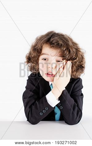 Little curly manager in a business suit sitting and holding both hands on the cheek. White background.