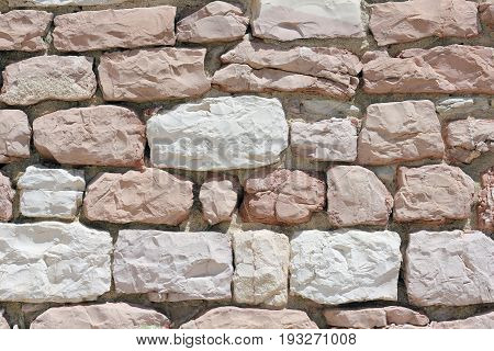 Wall made from white and pink limestone in Assisi in Italy