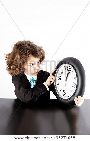 Little Curly Manager In A Business Suit Sadly Looks At His Watch. The Clock Shows Noon. White Backgr