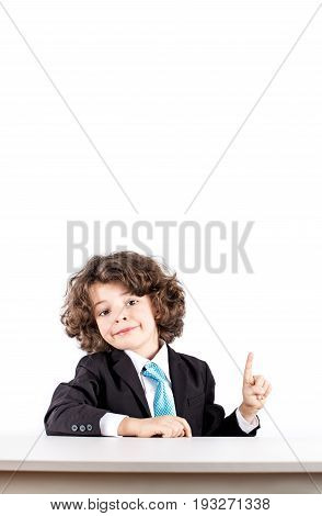 Little Curly Boy In A Business Suit Sitting At A Desk Smiling Out Points With The Index Finger Up. W