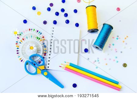 Blank  spiral notepad, sewing spools of blue and yellow caprone threads, plastic scissors, glass beds and colorful pins and pencils on white background. Space for text or message
