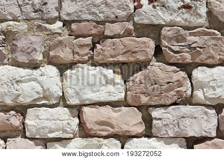 Limestone wall with white and pink stones in Assisi in Italy