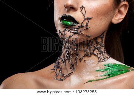 Woman with creative fashion make up on black background in studio photo. Cosmetics and extravagant makeup
