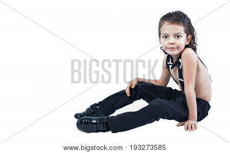 A Cute Boy In Suspenders Sits On The Floor And Looks Into The Camera. White Background.