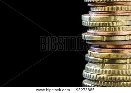 Stack of Euro coins over black.  Finance background with copy space.