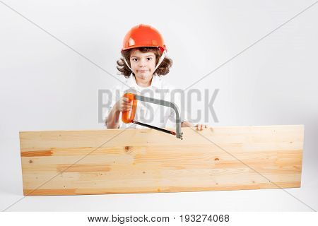 Young curly worker works with a hacksaw and board. Gray background.