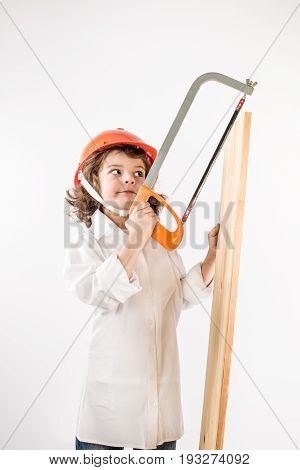 Little cute worker saws board with a hacksaw. Gray background.