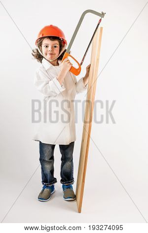 Little cute worker holding a hacksaw and board. Gray background.