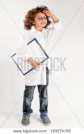 Little curly scientist smiling and looking at the camera. Gray background.