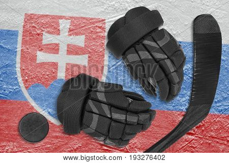 Hockey puck stick gloves and the image of the Slovak flag on the ice of the sports arena