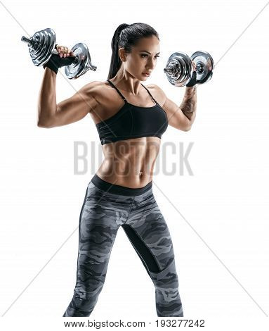 Sporty woman in training pumping up muscles of the back and hands with dumbbells. Photo of athletic young female isolated on white background. Strength and motivation