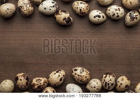 some quail eggs on the brown table. quail eggs frame with copy space. fresh quail eggs on the wooden background. lots of quail eggs background
