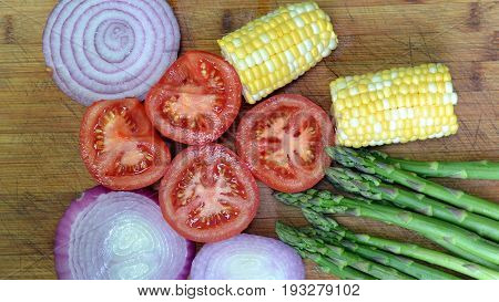 Red Onion Slices, Asparagus Spears, Tomato halves and Corn on the Cob prepared for Grilling on the BBQ. Making a Summer Salad.