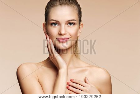 Smiling pretty woman with natural make-up looks at camera. Photo of young woman with perfect skin on beige background. Skin care and beauty