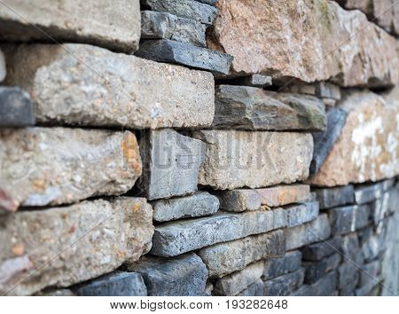 Old wall that is rough and weathered. Stone materials stacked in no particular order, yet sufficiently strong. Image reveals some fine textures.