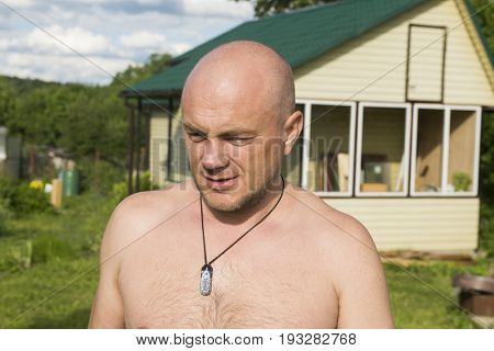 Bald man with a bare chest against the backdrop of a village house