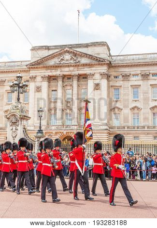 LONDON UNITED KINGDOM - JULY 11 2012: Officers and soldiers of the Coldstream Guards march in front of Buckingham Palace during the Changing of the Guard ceremony.