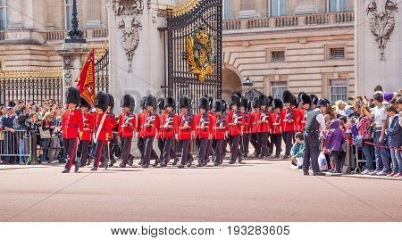 LONDON UNITED KINGDOM - JULY 11 2012: Officers and soldiers of the Scots Guards march out of Buckingham Palace during the Changing of the Guard ceremony.