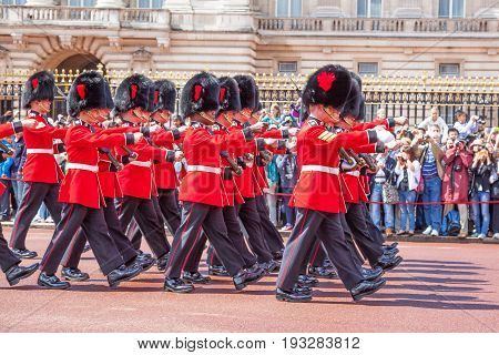 LONDON UNITED KINGDOM - JULY 11 2012: Soldiers of the Coldstream Guards march past the front of Buckingham Palace during the Changing of the Guard ceremony.