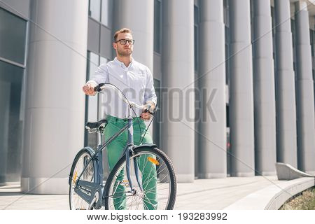 Cool young bearded hipster with bicycle on the city street. Smiling casual businessman having a break. He is standing in front of the building next to bike and holding laptop.