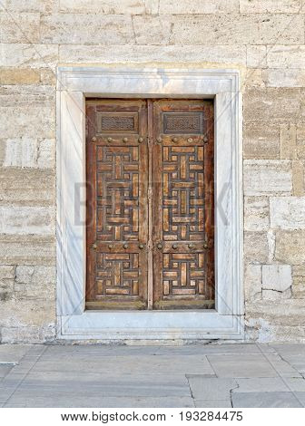 Wooden aged vaulted engraved door and exterior stone wall Sultan Ahmet Mosque Istanbul Turkey