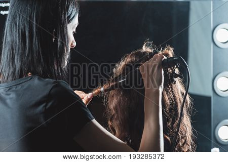 Hair Dresser Using Curling Iron While Styling Hair In Beauty Salon