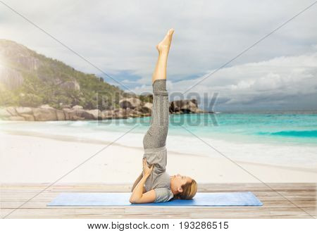 fitness, people and healthy lifestyle concept - woman making yoga in shoulderstand pose on mat over exotic tropical beach background