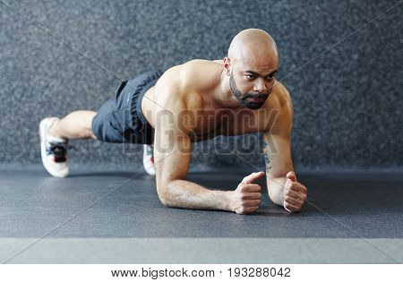 Motivational portrait of shirtless muscular man holding plank  against grey background, straining with effort and looking determined during intense endurance workout in gym