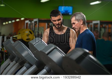 Senior man exercising on jogging machine in gym with assistance of personal trainer. Healthy lifestyle, fitness concept.