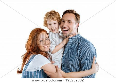 Happy Family With One Child Hugging And Smiling At Camera Isolated On White