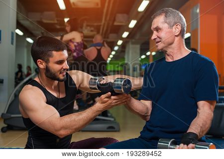 Happy smiling senior man and his personal trainer in gym. Male adult working out with coach. Healthy lifestyle, fitness and sports concept.