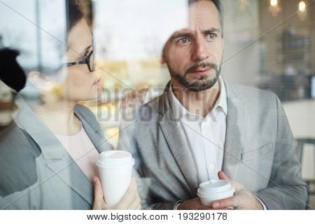 Woman with glass of drink reassuring worried colleague