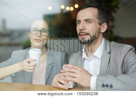 Two co-workers with drinks looking through cafe window