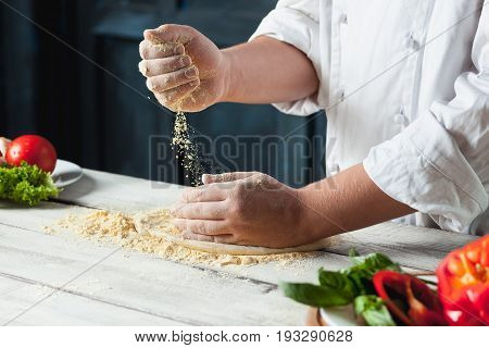 Closeup hand of chef baker in white uniform making pizza at kitchen or studio