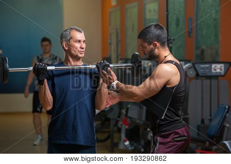 Young personal trainer working with senior man client in gym. Elderly man exercising with barbell. Healthy lifestyle, fitness and sports concept.