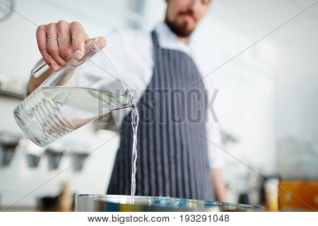 Chef pouring water from jug while cooking