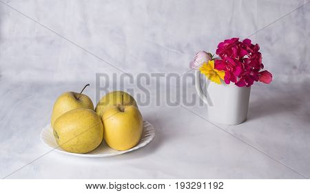 Apples and flowers in coffee cup on the table