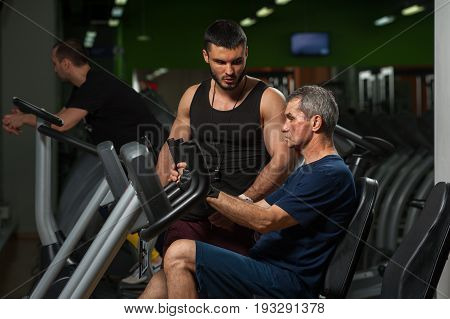 Senior man exercising on machine in gym with assistance of personal trainer. Healthy lifestyle, fitness concept.