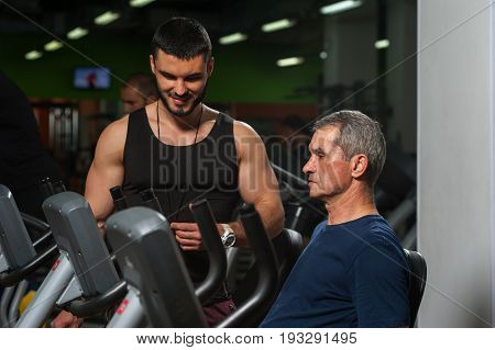 Senior man on exercising machine and his personal trainer. Male adult working out with coach in gym. Healthy lifestyle, fitness and sports concept.
