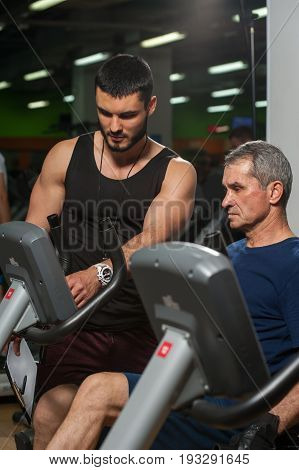 Young personal trainer working with senior man client in gym. Elderly man exercising on machine. Healthy lifestyle, fitness and sports concept.