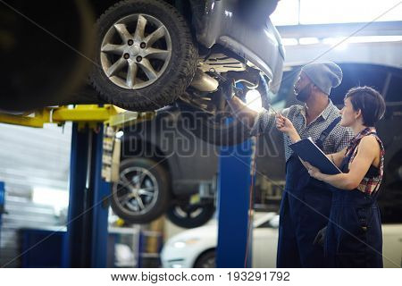 Master of car service consulting his trainee in workshop