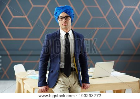 Handsome man in suit and blue turban looking at camera