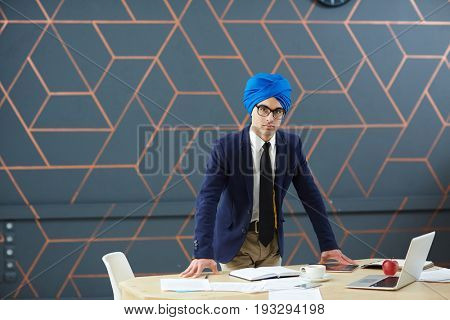 Serious businessman leaning at workplace