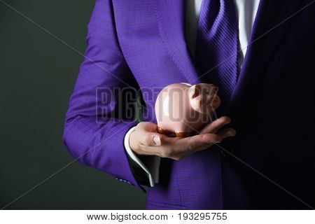 Pink Piggy Bank For Saving Money Standing On Male Hand