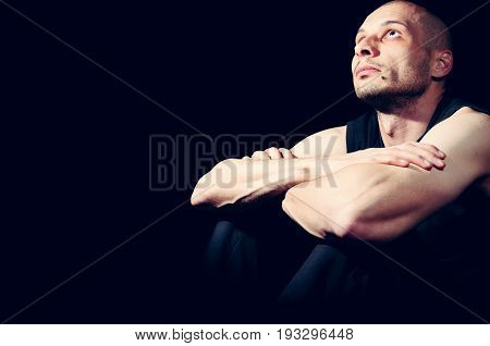 Loneliness. Young lonely man search for God. Dark image. Black background.