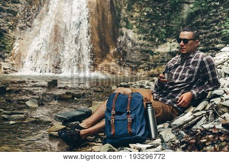 Backpacker Man Drink Tea Or Coffee From Thermos On Waterfall Background Resting Camping Destination Travel Concept