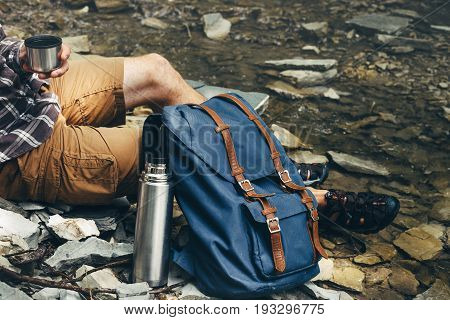 Unrecognizable hiker man drink tea or coffee from thermos Hiking Resting Concept