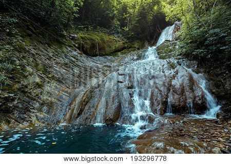 Traveler Explorer Enjoys View Of Waterfall In Deep Forest In Summer Rear View